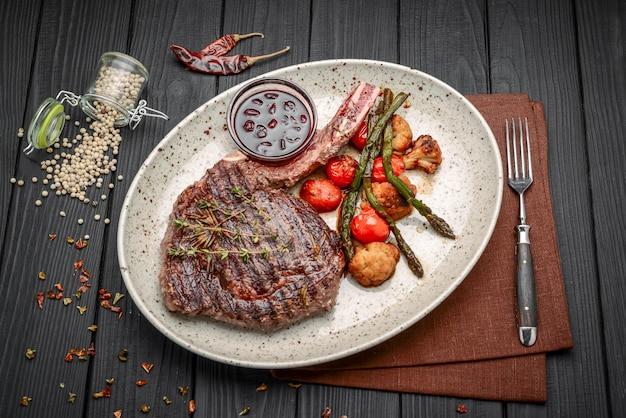 Carnes grelhadas e legumes na mesa de madeira rústica