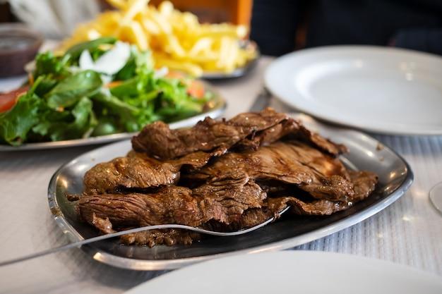 Carnes grelhadas em prato na mesa de restaurante