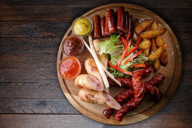 Carnes variadas e salsichas, com batatas fritas em uma placa de madeira