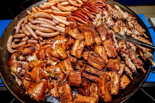 Carnes variadas. salsichas grelhadas, costelas, pernil em uma frigideira grande.