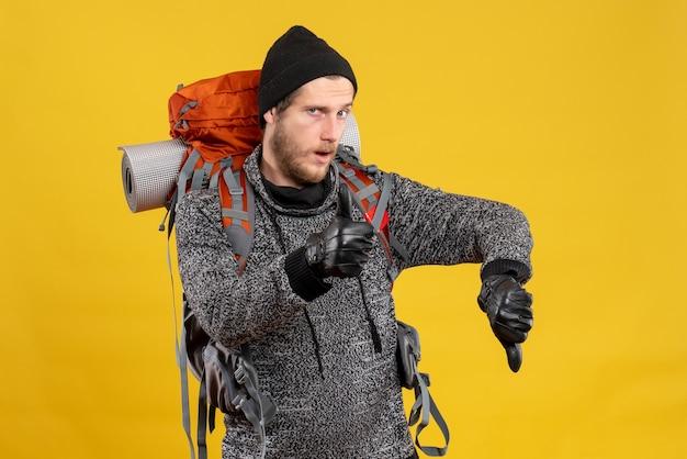 Carona masculino com luvas de couro e mochila dando sinal de subida e descida com o polegar