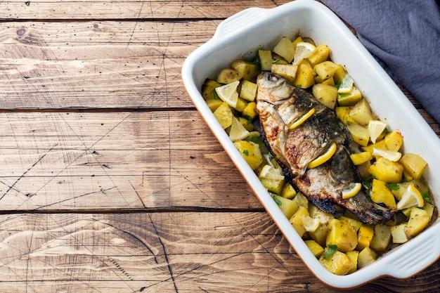 Carpa cozida dos peixes com batatas em uma bandeja cerâmica. estilo rústico. espaço da cópia