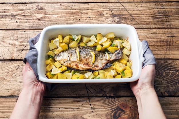 Carpa cozida dos peixes com batatas em uma bandeja cerâmica. estilo rústico.