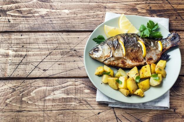 Carpa cozida dos peixes com verdes e batatas do limão em uma placa. fundo de madeira espaço da cópia