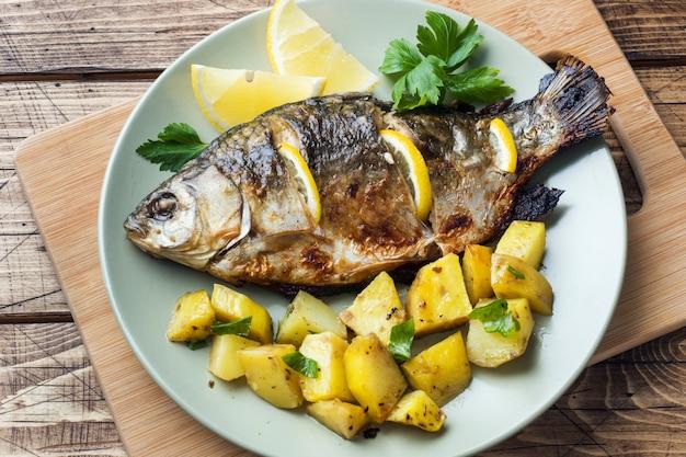 Carpa cozida dos peixes com verdes e batatas do limão em uma placa. fundo de madeira