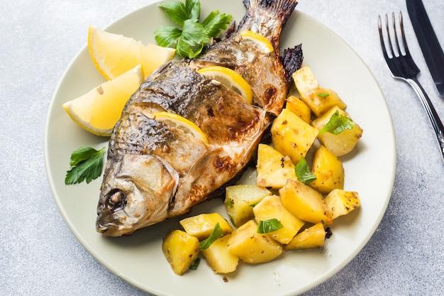 Carpa cozida dos peixes com verdes e batatas do limão em uma placa.