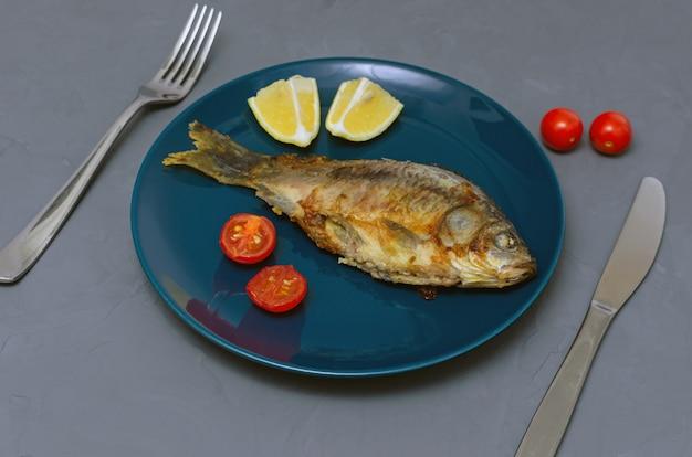 Carpa crucian de peixe apetitoso frito com tempero em um prato azul em uma mesa cinza decorada com fatias de tomate e limão com uma faca e um garfo. conceito de alimentação saudável.
