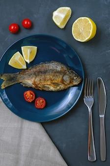 Carpa crucian de peixe apetitoso frito com tempero em um prato azul em uma mesa cinza decorada com fatias de tomate e limão com uma faca e um garfo. quadro vertical.