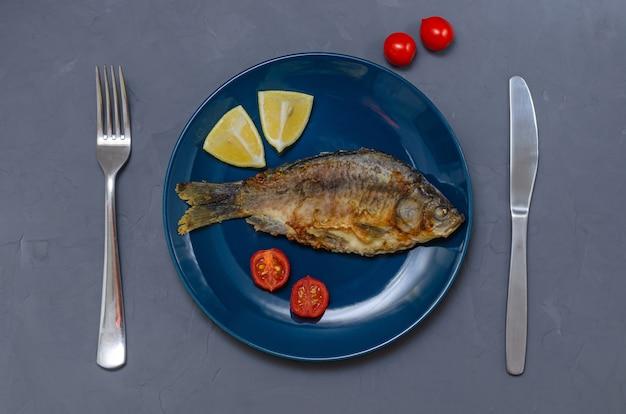 Carpa crucian de peixe apetitoso frito com tempero em um prato azul em uma mesa cinza decorada com fatias de tomate e limão com uma faca e um garfo.