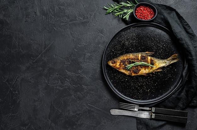 Carpa crucian grelhada em um prato branco. peixe orgânico do rio. vista do topo. copyspace fundo