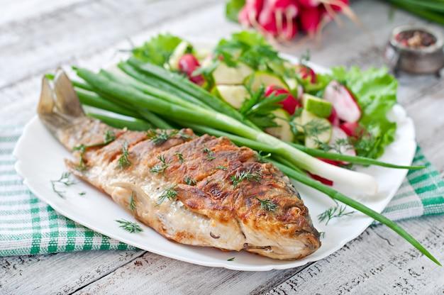 Carpa de peixe frito e salada de legumes frescos