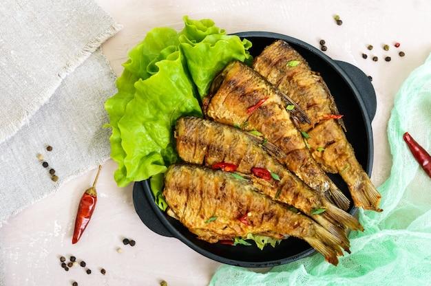 Carpa de peixe frito (sazan) em uma frigideira de ferro fundido com folhas de alface. vista do topo.