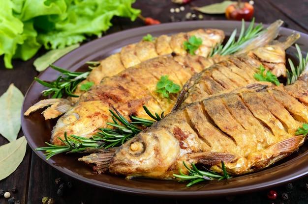Carpa de peixe frito (sazan) em uma tigela de cerâmica com ramos de alecrim em uma mesa de madeira escura. fechar-se