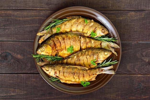Carpa de peixe frito (sazan) em uma tigela de cerâmica com ramos de alecrim em uma mesa de madeira escura. vista do topo.