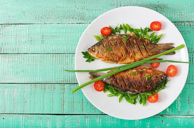 Carpa fritada dos peixes e salada do legume fresco no fundo de madeira.