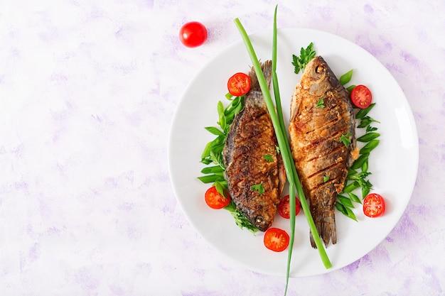 Carpa fritada dos peixes e salada do legume fresco.