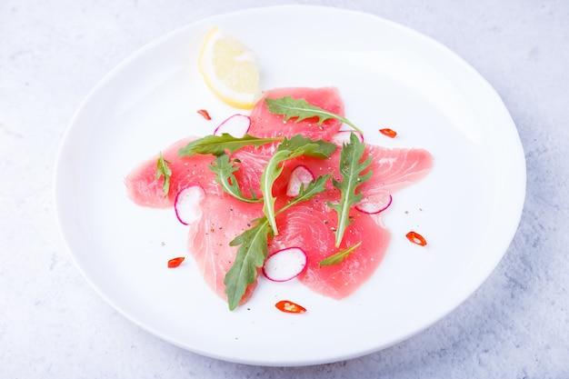 Carpaccio de atum fresco com rúcula, rabanete, pimenta e limão. aperitivo frio tradicional da culinária italiana. close-up, foco seletivo.