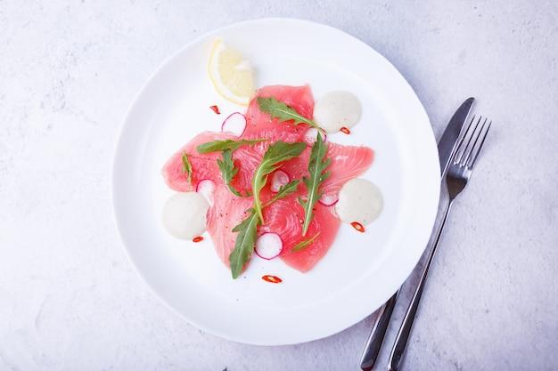 Carpaccio de atum fresco com rúcula, rabanete, pimenta, limão e molho. aperitivo frio tradicional da culinária italiana. close-up, foco seletivo, vista superior.