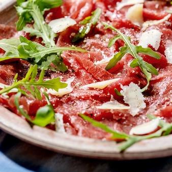 Carpaccio de carne clássico com queijo e rúcula em prato de cerâmica sobre toalha de mesa branca e azul. imagem quadrada
