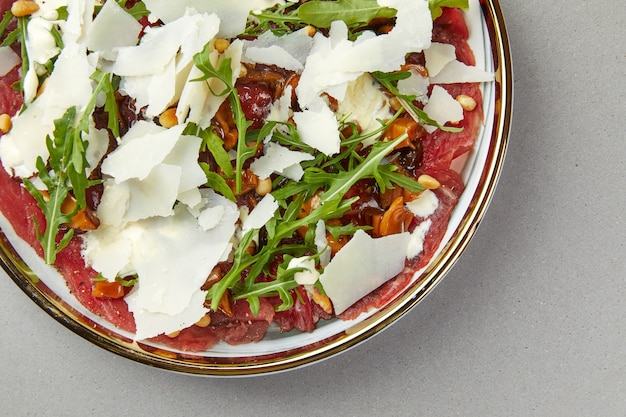 Carpaccio de carne com rúcula e queijo parmesão