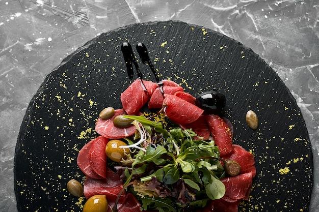 Carpaccio de carne com rúcula em uma placa preta, cozinha tradicional italiana. tecla escura, copie o espaço,