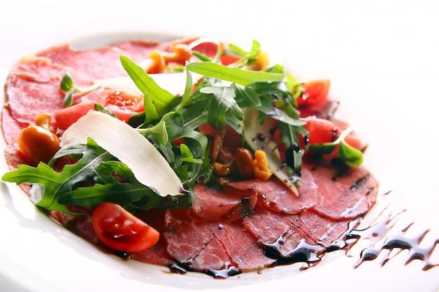 Carpaccio de carne de bovino servido com rúcula
