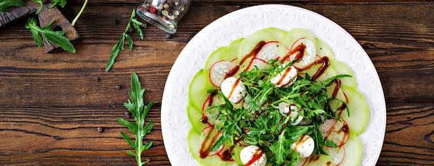 Carpaccio de rabanete com rúcula, mussarela e molho balsâmico. comida saudável. salada daikon. postura plana. vista do topo