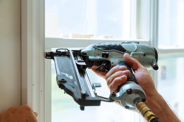 Carpenter brad usando pistola de pregos para molduras nas janelas, emoldurando guarnição