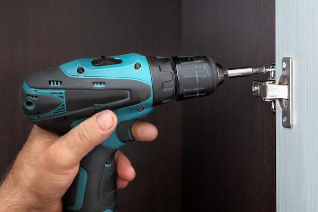 Carpenter instala armários de porta, chave de fenda sem fio de dobradiça de porta de parafuso.