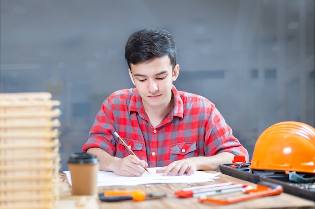 Carpenter men diy drill in home barbudo bonito marceneiro na mesa com lápis desenho sinal na prancha.