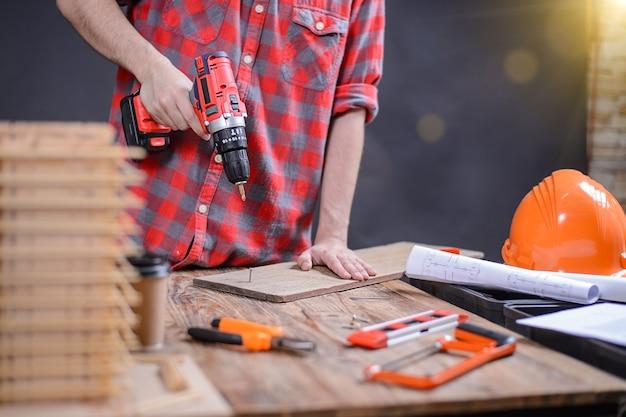 Carpenter men diy perfura em casa marceneiro barbudo bonito na mesa