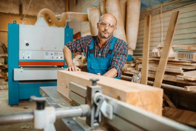 Carpenter processa viga de madeira em máquina plana, marcenaria, indústria madeireira, carpintaria. processamento de madeira em fábrica de móveis