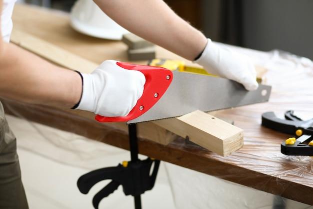 Carpenter usa serra que está cortando em ângulo. serrar tipo que requer uso de equipamento especial. fabricar pequenos produtos inteiros ou peças individuais com a montagem subsequente. processamento de madeira especial