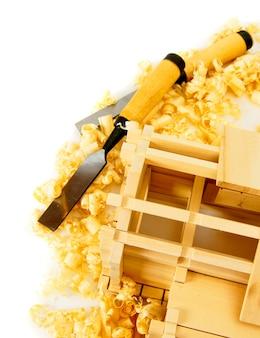 Carpintaria. construção de casas. obras de marceneiro. a casa de madeira, formão e corte em fundo branco.