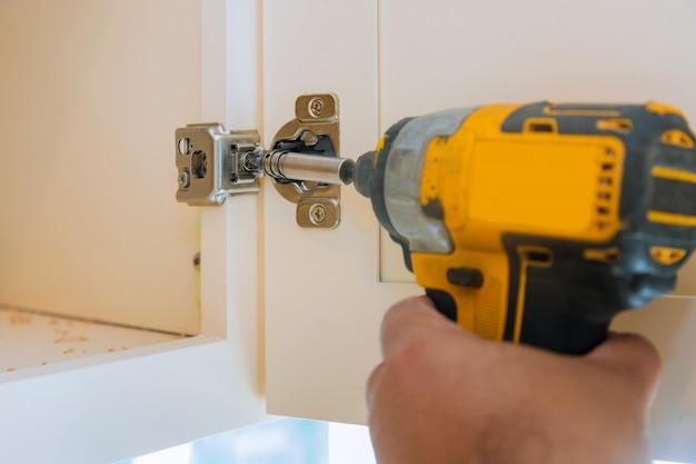 Carpintaria montagem de acessórios para móveis na porta da cozinha com dobradiça para um armário de cozinha, uma chave de fenda.