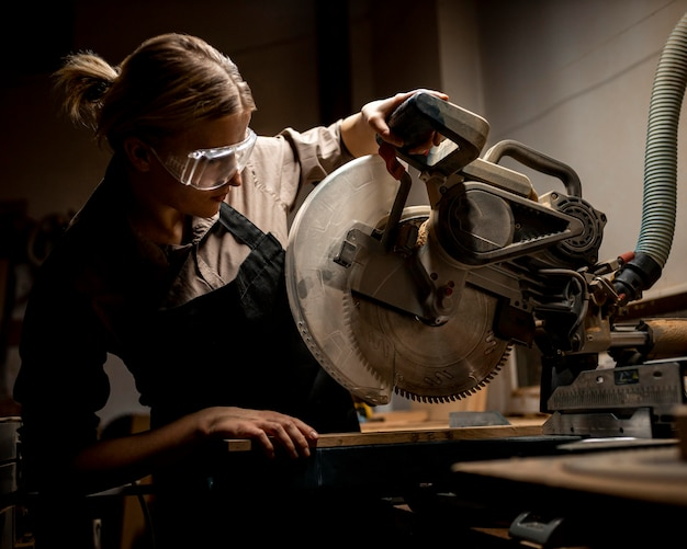 Carpinteira com óculos de segurança e ferramenta