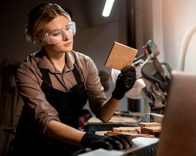 Carpinteira com óculos de segurança olhando um pedaço de madeira no estúdio