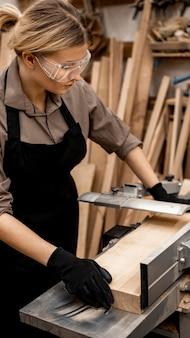 Carpinteira com óculos de segurança serrando madeira