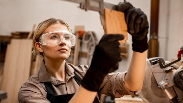 Carpinteira com óculos usando ferramenta para medir madeira