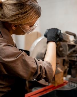 Carpinteira com óculos usando serra elétrica