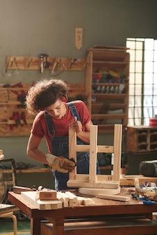 Carpinteira concentrada usando protetores de ouvido e luvas de proteção polindo cuidadosamente um banco de madeira virado para cima na mesa