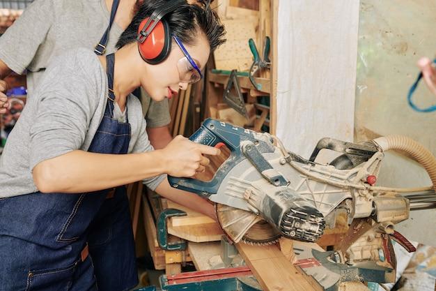 Carpinteira cortando madeira