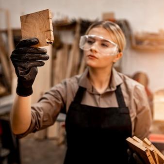 Carpinteira de óculos olhando um pedaço de madeira