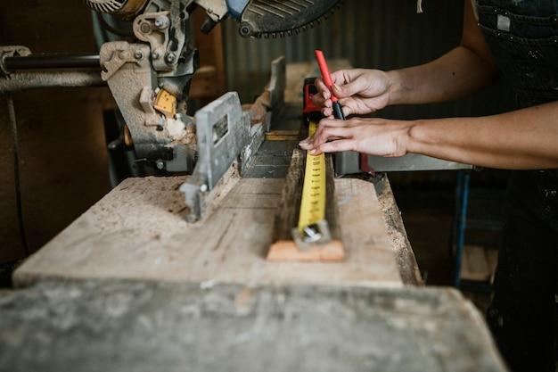 Carpinteira medindo madeira serrada