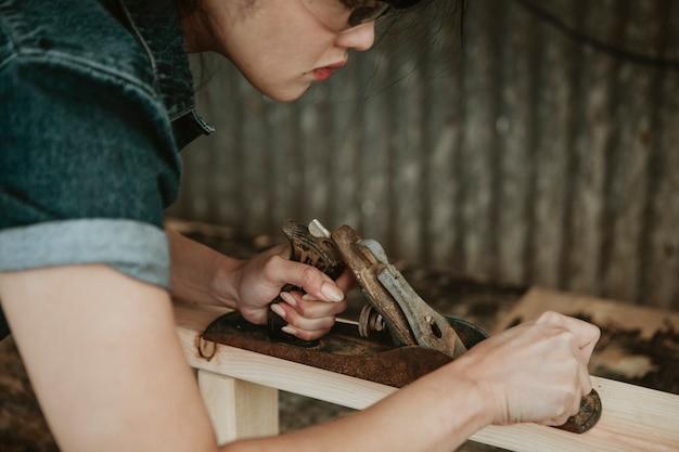 Carpinteira modelando madeira serrada com uma plaina manual