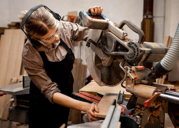 Carpinteira no estúdio usando serra elétrica