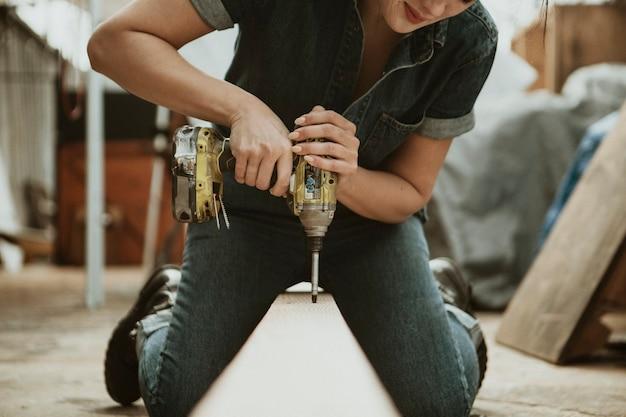 Carpinteira perfurando uma madeira