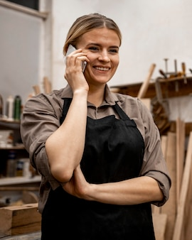 Carpinteira sorridente usando smartphone no trabalho