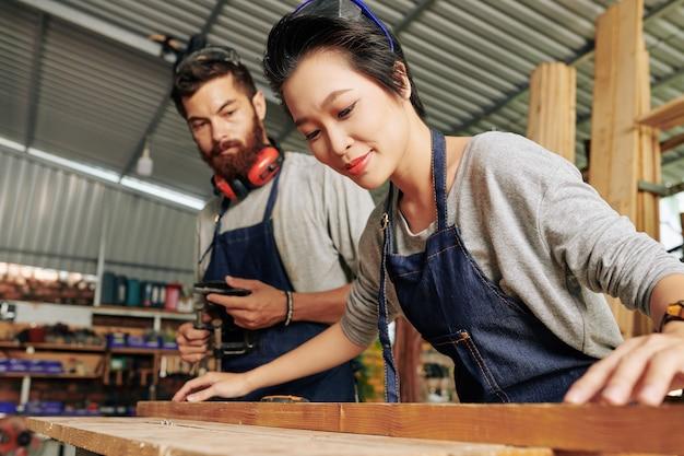 Carpinteira trabalhando com madeira