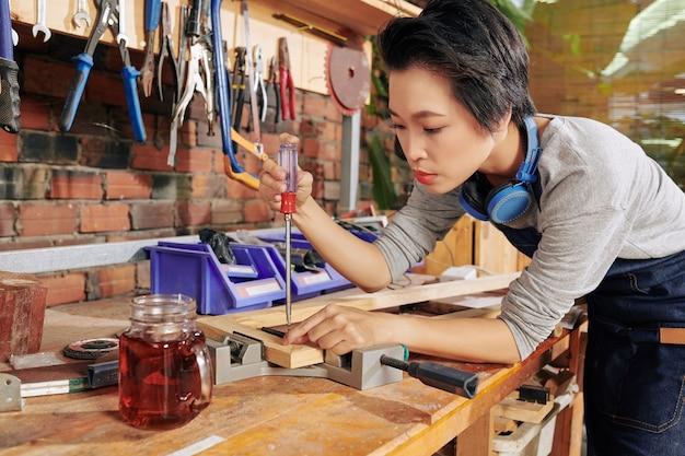 Carpinteira vietnamita concentrada usando uma chave de fenda e um torno para unir pranchas de madeira